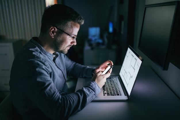 Jovem empresário caucasiano com óculos usando telefone inteligente