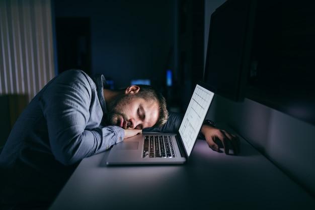 Jovem empresário caucasiano dormindo no escritório tarde da noite.