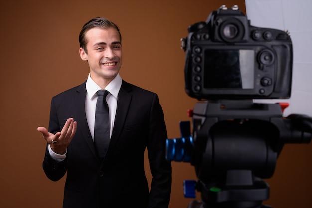 Jovem empresário caucasiano feliz fazendo vlogs em estúdio