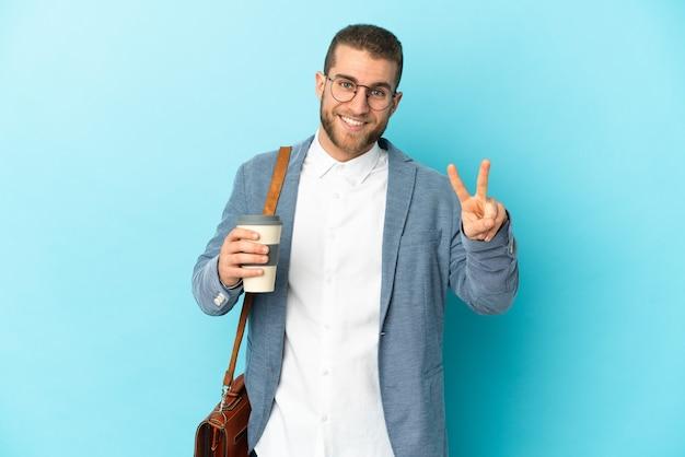 Jovem empresário caucasiano isolado em um azul, sorrindo e mostrando sinal de vitória