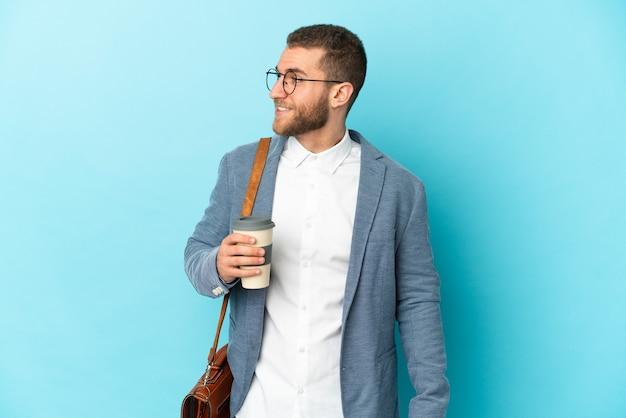 Jovem empresário caucasiano isolado em um fundo azul, olhando para o lado e sorrindo