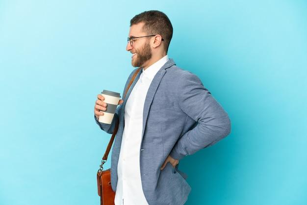 Jovem empresário, caucasiano, isolado em uma parede azul, sofrendo de dor nas costas por ter feito um esforço