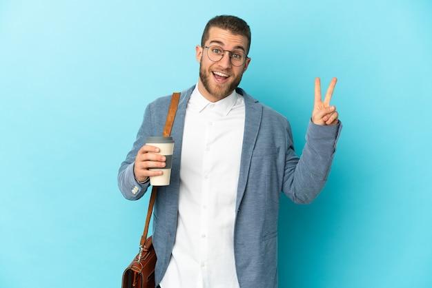 Jovem empresário caucasiano isolado na parede azul sorrindo e mostrando o sinal da vitória