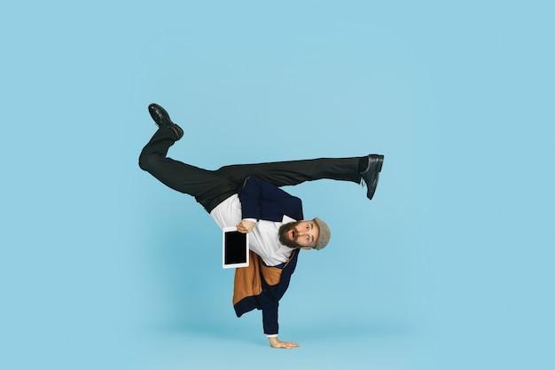 Jovem empresário caucasiano se divertindo dançando a dança break no fundo azul do estúdio.