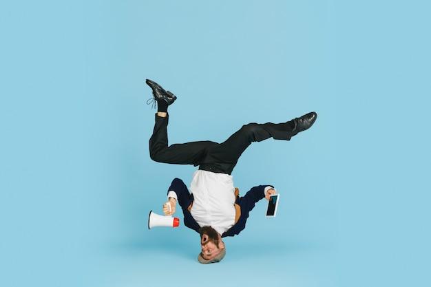 Jovem empresário caucasiano se divertindo, dançando a dança break no fundo azul do estúdio.
