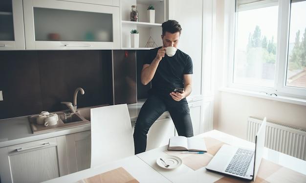 Jovem empresário caucasiano trabalhando em casa usando telefone e laptop com um livro, bebendo um café enquanto faz uma pausa na cozinha