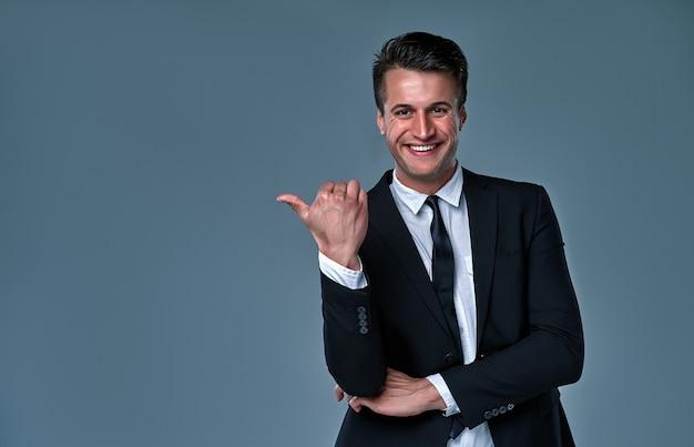 Jovem empresário caucasiano vestindo terno em pé sobre um fundo cinza isolado, sorrindo com uma cara feliz, olhando e apontando para o lado com o polegar para cima.
