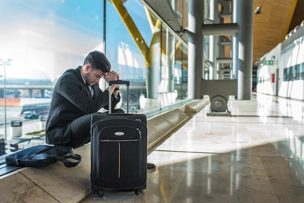 Jovem empresário chateado no aeroporto esperando seu voo atrasado com bagagem