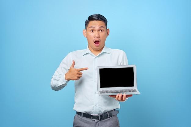 Jovem empresário chocado apontando para um laptop com uma tela em branco sobre fundo azul