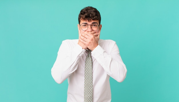 Jovem empresário cobrindo a boca com as mãos com uma expressão chocada e surpresa, mantendo um segredo ou dizendo oops