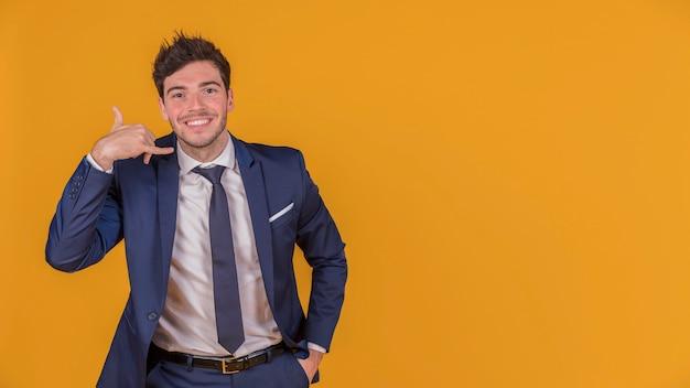 Jovem empresário com a mão no bolso fazendo gesto de chamada contra um pano de fundo laranja
