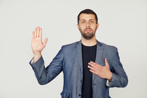 Jovem empresário com barba em um casaco, jura, colocando a mão no peito e a palma da mão aberta, fazendo um juramento de promessa de lealdade.