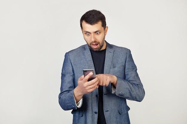 Jovem empresário com barba em uma jaqueta usando um smartphone assustado chocado com uma cara de surpresa