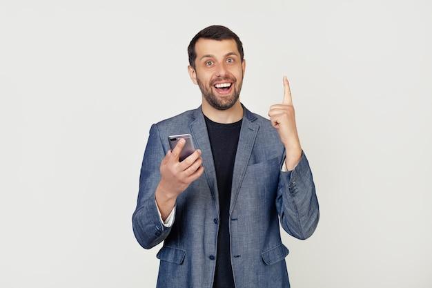 Jovem empresário com barba em uma jaqueta usando um smartphone surpreso com uma ideia ou pergunta