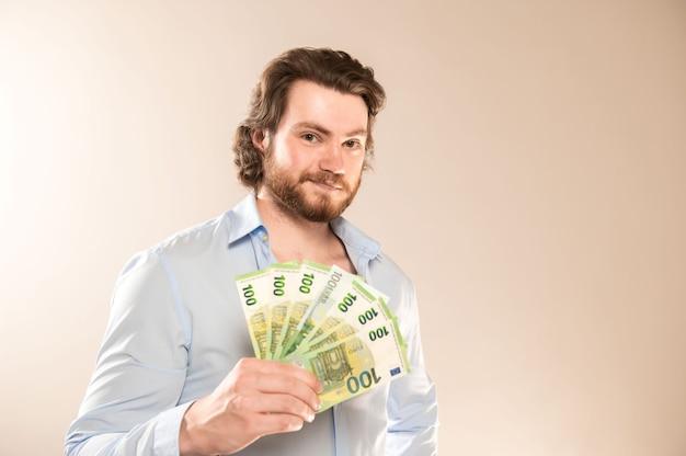 Jovem empresário com barba nas mãos de dinheiro em um fundo cinza