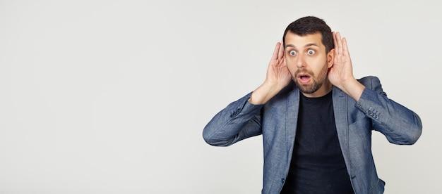 Jovem empresário com barba tenta ouvir as duas mãos em seu ouvido, curioso sobre a fofoca.