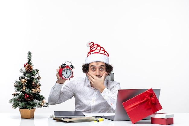 Jovem empresário com chapéu de papai noel e mostrando o relógio pensando em algo com cuidado e sentado no escritório no fundo branco