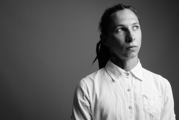 Jovem empresário com dreadlocks contra uma parede cinza em preto e branco