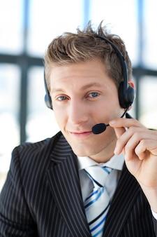 Jovem empresário com fone de ouvido em um call center