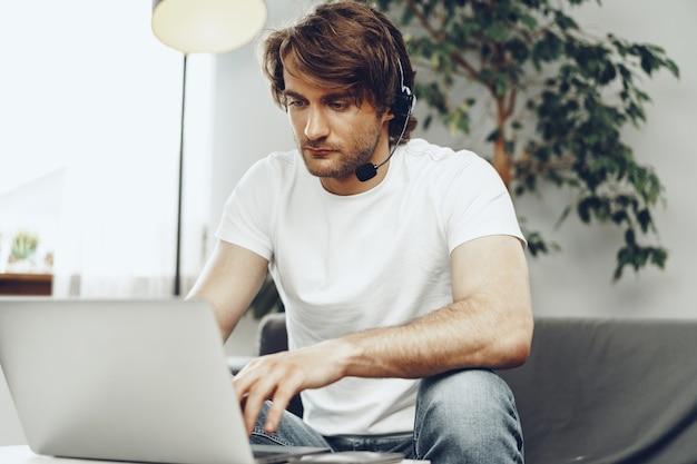 Jovem empresário com fone de ouvido trabalhando em um laptop de casa