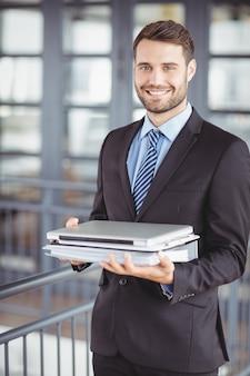 Jovem empresário com laptop e documentos no escritório
