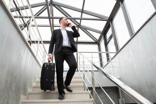 Jovem empresário com mala em um terno elegante falando ao telefone enquanto caminhava pelas escadas em um prédio comercial moderno