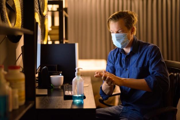 Jovem empresário com máscara usando desinfetante para as mãos enquanto trabalha em casa à noite