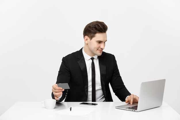 Jovem empresário com notebook e cartão de crédito isolado sobre fundo branco.