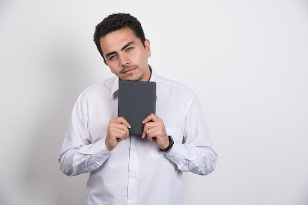 Jovem empresário com notebook posando em fundo branco.