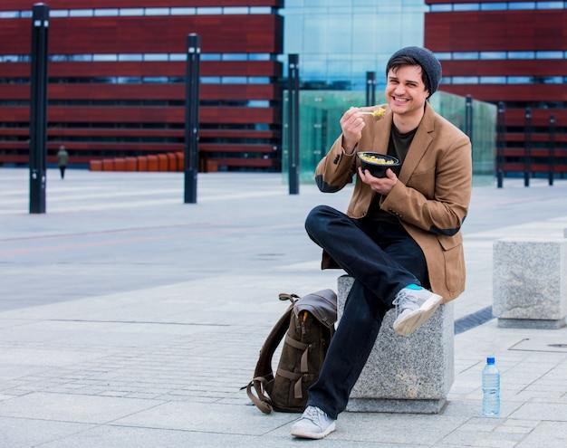 Jovem empresário com salada na cidade urbana ao ar livre