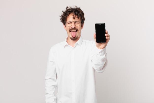 Jovem empresário com um celular com atitude alegre e rebelde, brincando e mostrando a língua