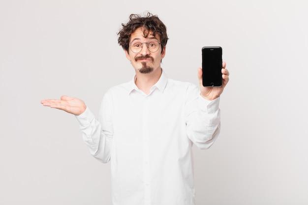 Jovem empresário com um celular se sentindo perplexo, confuso e em dúvida