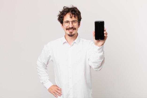 Jovem empresário com um celular sorrindo feliz com uma mão no quadril e confiante