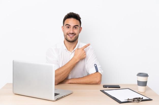 Jovem empresário com um telefone móvel em um local de trabalho, apontando o dedo para o lado
