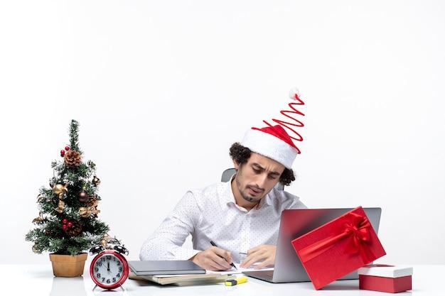Jovem empresário concentrado com chapéu de papai noel engraçado, verificando a escrita de bilhetes comemorando o natal no escritório em fundo branco