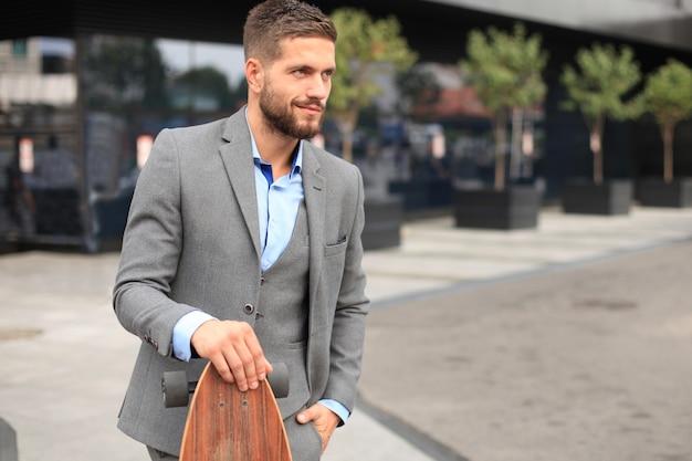 Jovem empresário confiante andando na rua, usando longboard.
