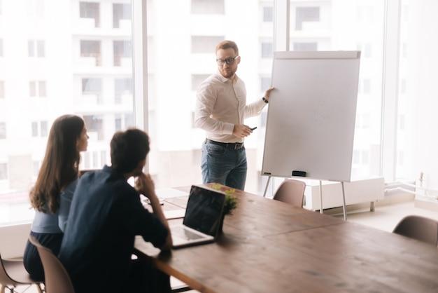 Jovem empresário confiante apresentando novo projeto para parceiros no quadro branco