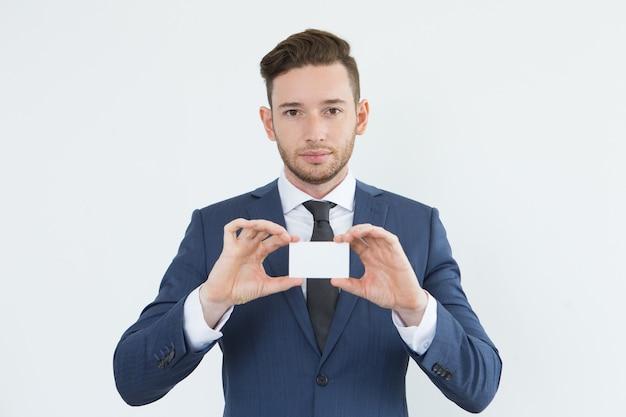 Jovem empresário confiante e sortudo que mostra o cartão