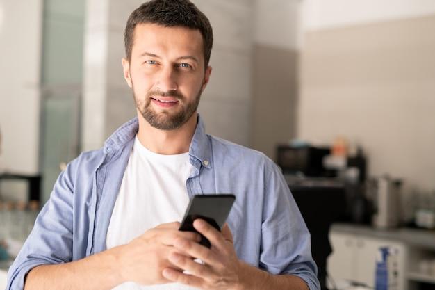Jovem empresário confiante em roupas casuais em pé no café enquanto rola a tela ou envia mensagens de texto no smartphone