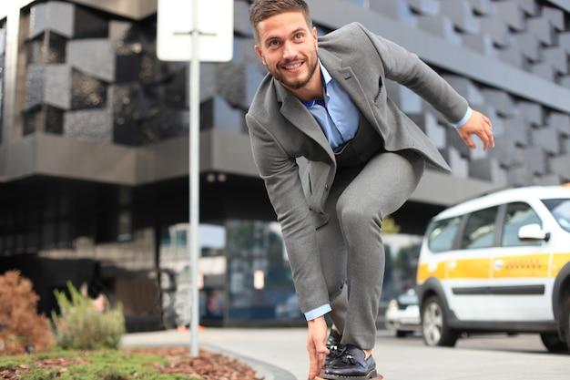 Jovem empresário confiante em um terno de negócio no longboard, apressando-se para o escritório, na rua da cidade