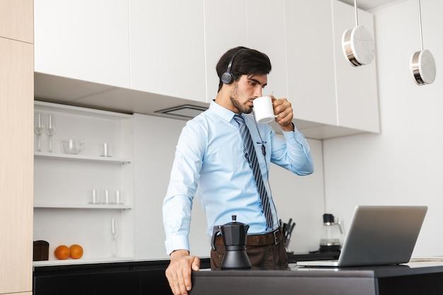 Jovem empresário confiante trabalhando em casa na cozinha, usando um laptop, comunicando-se por meio de fone de ouvido