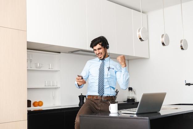 Jovem empresário confiante trabalhando em casa na cozinha, usando um laptop