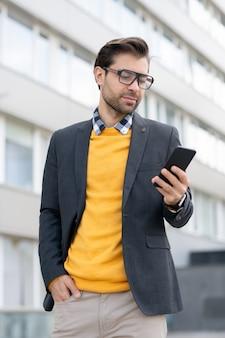 Jovem empresário contemporâneo em smart casual olhando para a tela do smartphone na mão enquanto procura o contato