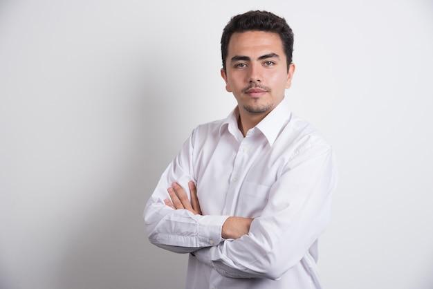 Jovem empresário, cruzando os braços em fundo branco.