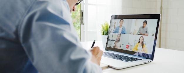 Jovem empresário da ásia usando laptop fala com colegas sobre o plano de uma reunião de videochamada enquanto trabalha em casa na sala de estar. auto-isolamento, distanciamento social, quarentena para prevenção do vírus corona.