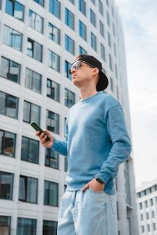 Jovem empresário da moda com smartphone no centro de negócios