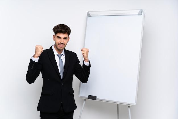 Jovem empresário, dando uma apresentação no quadro branco, comemorando uma vitória