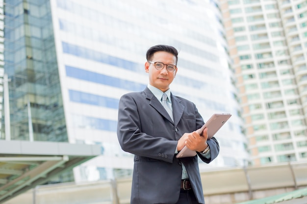 Jovem empresário de ásia no terno com o seu computador portátil ao ar livre