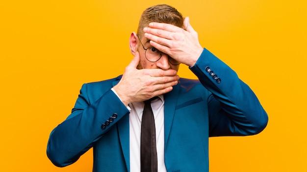 Jovem empresário de cabeça vermelha, cobrindo o rosto com as duas mãos, dizendo não à câmera! recusar fotos; proibir fotos laranja