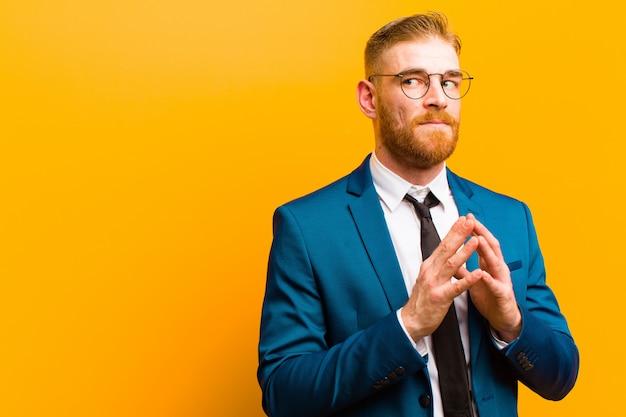 Jovem empresário de cabeça vermelha, conspirando e conspirando, pensando em truques e fraudes tortuosos, astúcia e traição contra a laranja